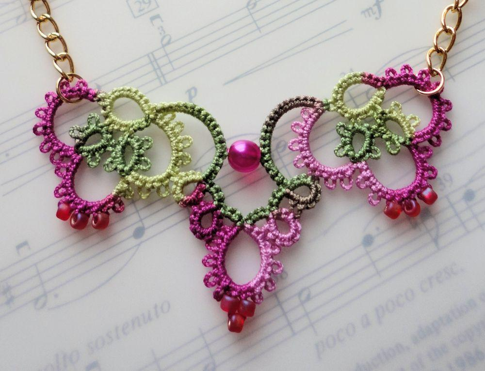 crochet jewelry pink crochet necklace laying on music book CNRXBMH